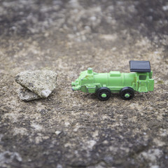 Green steel toy train route interrupted by a stone, conceptual photo