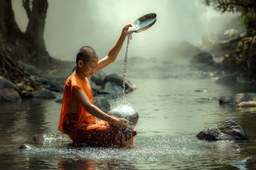 Thailand monk or novice monk sitting in the creek are wash container or bowl to clean