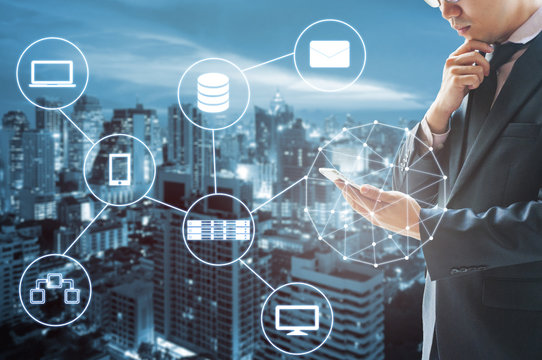 Double exposure of businessman connected internet and wireless network with his smart phone and city of business background in business trading and technology concept