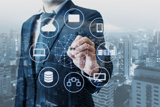 Double exposure of businessman connected devices with world digital technology internet and wireless network on touch screen and city of business background in business and technology concept