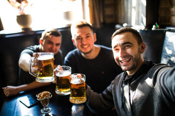 happy male friends drinking beer and taking selfie with smartphone at bar or pub