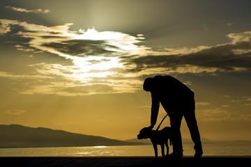 Genç adam ve köpeği silüet