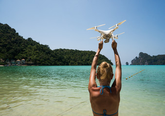 Back view of woman standing on the beach with raised hands holding drone over beautiful sea and summer blue sky background