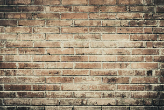 Old brick wall with cracks and scratches. Horizontal wide brickwall background. Distressed wall with broken bricks texture. House facade. Vintage filter.