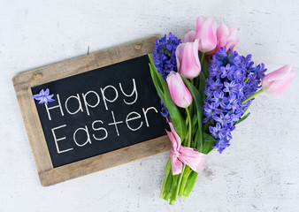 Pink tulips and blue hyacinths flowers bouquet on white wooden table with blackboard and happy easter greetings