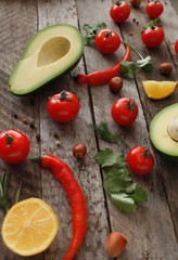 Avocado with ingredients and spices to avocado paste or guacamole. Avocado,Parsley, Chili pepper, Cherry Tomatoes on a wood Background.Food or Healthy diet concept.Vegetarian. selective focus.