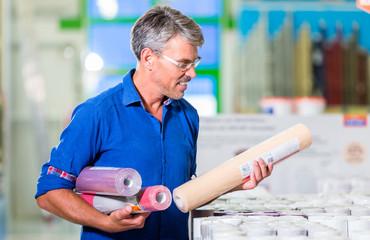 Vater sucht im Baumarkt Tapeten für ein Mädchenzimmer aus