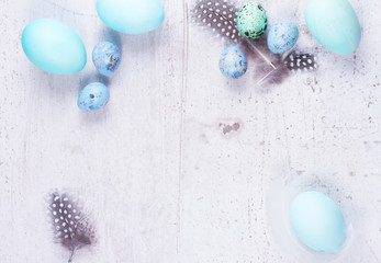 Painted Blue easter eggs frame on white aged wooden tabletop with copy space