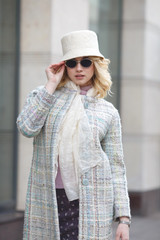 A beautiful stylish blond woman in a coat and hat and sunglasses on a city street.