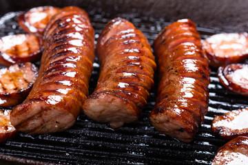 Fried pork sausages on a cast iron skillet.