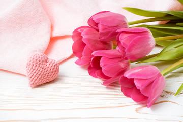 Букет розовых тюльпанов и вязанное сердце на столе