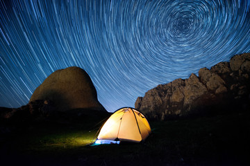Star circles above the mountains and a glowing tent