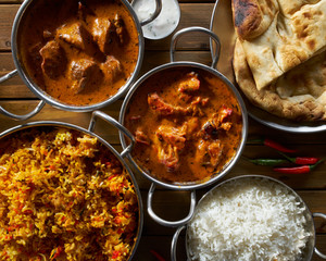 assorted indian curry and rice dishes in flat lay composition