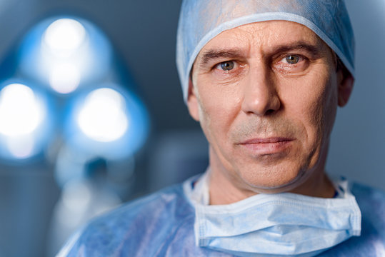 Serious doctor standing in operating room