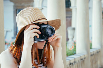 Beautiful girl in hat and sunglasses holding old camera