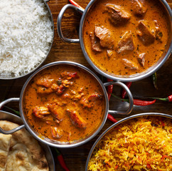 assortment of indian curry and rice dishes shot from overhead composition