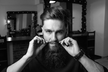 Brutal bearded man fixes his mustache