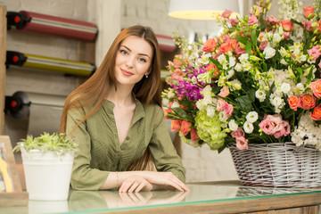 Beautiful female florist at her flower shop