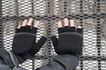 Men's gloved hands lie on a metal net