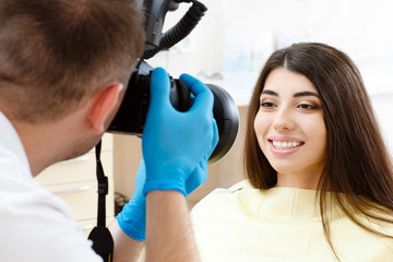 Dentist taking pictures of the teeth of his client with his camera