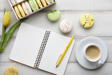 Woman's flat lay workspace with notebook, macarons, yellow tulips and a cup of coffee