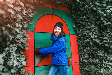 Beautiful young woman standing near retro fairy tale door