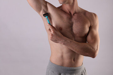 Male depilation. Young attractive muscular man using razor to remove hair from his armpit