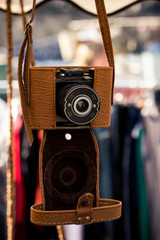 A retro camera with a light leater case hanging.