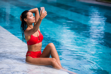 Beautiful woman in bikini taking a selfie by pool side on a sunny day at luxury hotel
