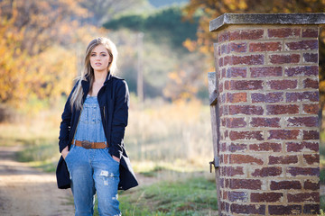 Senior photo of a girl on a farm wearing farm style clothing