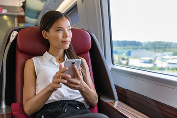 Asian woman relaxing in train seat while using smartphone app. Chinese businesswoman enjoying view texting on mobile phone. Travel lifestyle.