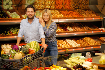 Beautiful couple strolling at the market with the shopping cart