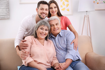 Young couple with middle aged parents on sofa in the room