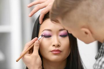 Male artist doing makeup for model in salon