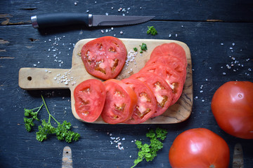 Sliced tomato on cutting board with parsley and salt