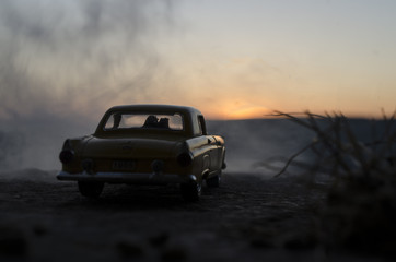 silhouettes of Happy Couple sitting in old vintage car at sunset time. Toy installation effect like reality. Selective focus