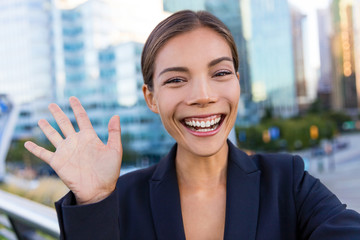 Business woman taking selfie photo using smart phone app on smartphone for social media. Young businesswoman using smartphone smiling happy wearing suit jacket outdoors. Urban female professional.