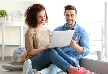 Happy young couple with laptop at home