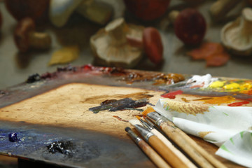 The workplace of the artist, brushes, paints and canvas. Multicolor oil paints on a palette close up.