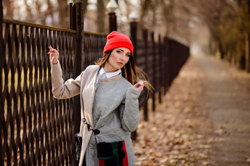 Beautiful girl in a red cap walks through the city