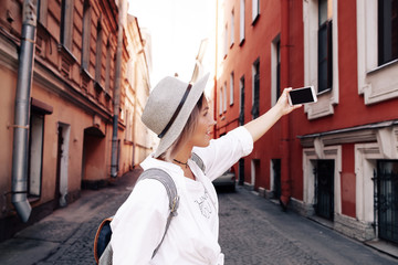 Happy young female traveler taking selfie on street. Travel concept