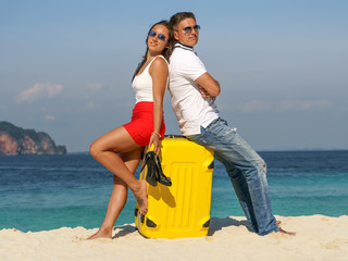 Young couple of tourists on a tropical beach with a suitcase