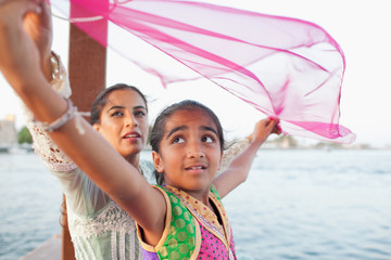 Mother with daughter traveling on boat at Dubai Creek.
