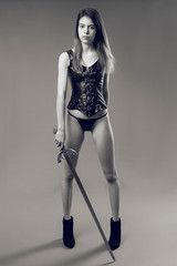 Attractive girl poses with leather corset and medieval sword