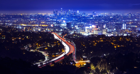 Los Angeles city skyline and highway 101 viewed from West Hollywood hills or heights. Trails of light from cars and traffic.
