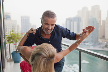 Couple dancing at balcony.