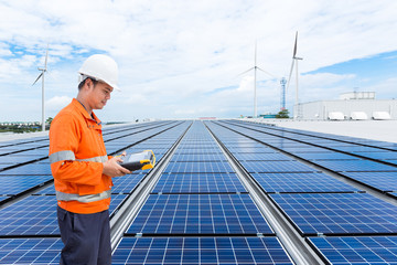 Engineer checking solar panels on factory roof