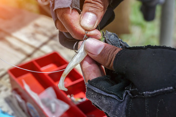 Angler tying a fishing hook to rubber worm lure