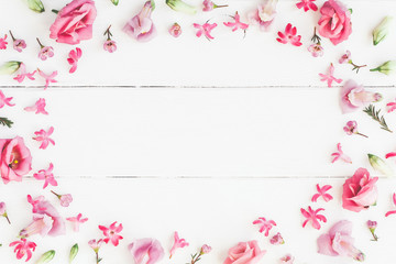 Flowers composition. Frame made of various pink flowers on wooden white background. Flat lay, top view