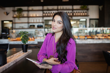 Portrait of woman with digital tablet at restaurant.